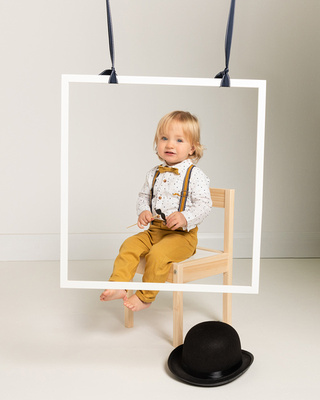 Toddler boy in smart outfit sits on a chair surrounded by photo booth props