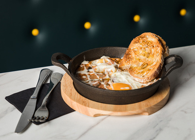 A breakfast skillet photographed on marble tabletop with knife. fork and napkin