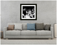Framed black & white print of a family hung above a grey sofa