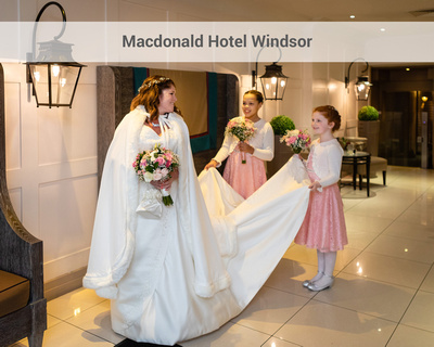 Bride dressed for winter with a fur cloak smiles at her two young bridesmaids in the entrance of the Macdonald Hotel Windsor