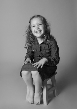 Girl sits on a stool and giggles, photographed in a studio sitting