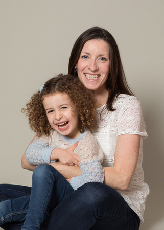 Mother & daughter giggle on studio photoshoot