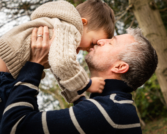 Father lifts son high and kisses him surrounded woodland