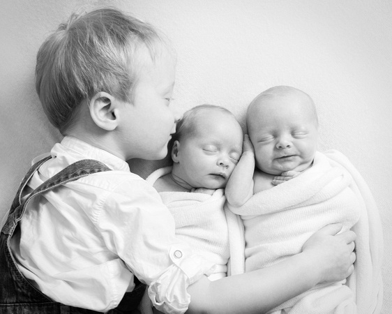 Toddler boy kisses and hugs his newborn twin baby siblings