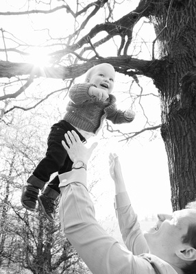 toddler being thrown in the air by his father during a family photoshoout outdoors