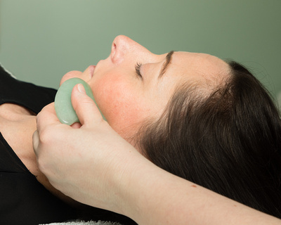 GuaSha being used during a\ Zone Face Lift facial reflexology treatment