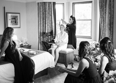 bride having hair and make up done as bridesmaids look on