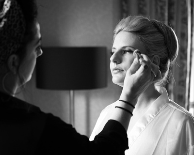bride photographed in beautiful light having her make up finished for her wedding