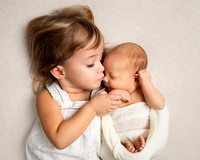 A toddler gently cuddles her newborn baby brother during a natural baby photoshoot