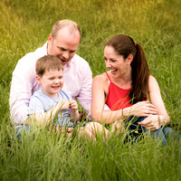 Family photographed laughing together sat amongst long grass
