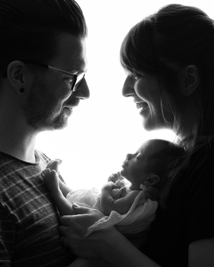 Parents with newborn baby photographed in semi-silhouette, backlit by a studio flash