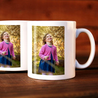 Two mugs with a photo on them of a girl dressed in pink and blue looking at trees, the mugs are sat on a table.