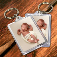 Two keyrings containing a photo of a baby yawning on a wooden tabletop.