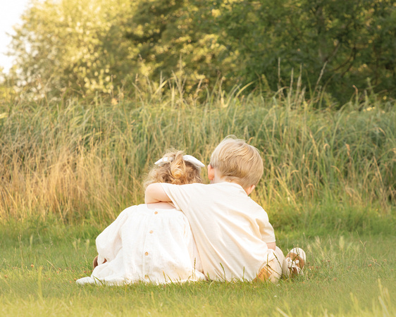 A 3-year-old boy and girl hug in a long grass meadow with their backs to the camera
