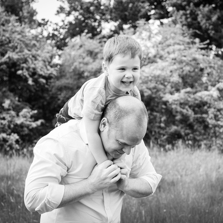 Dad carries son on his shoulders - outdoors, photographed in black & white