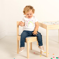 Toddler girl modelling jeans and t-shirt looks down and smiles whilst sat on a chair at a small table surrounded by confetti