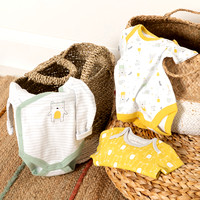 Three baby vests laid out on wicker baskets