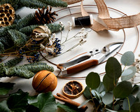 Elements of a wreath-making kit (pine, ribbon, wire, circle, dried orranges, etc) laid out on a white surface